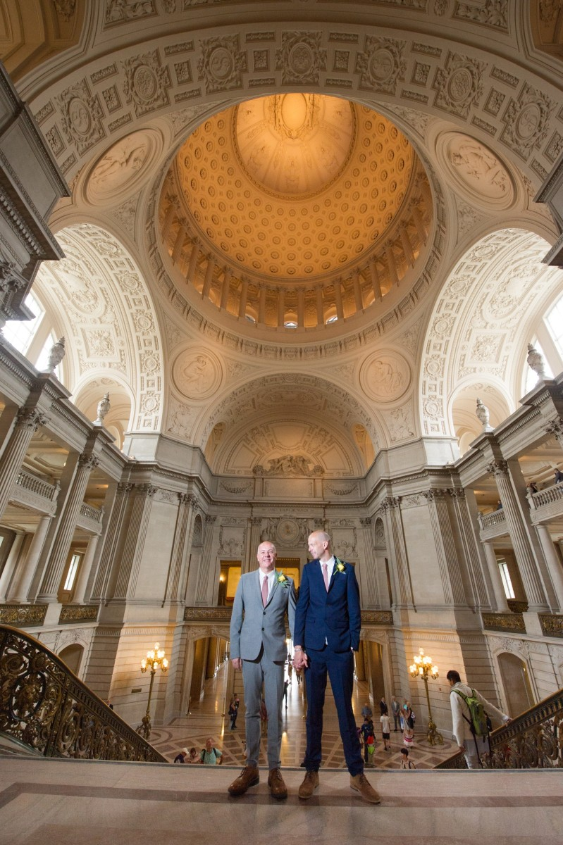 Two marriers in suits stand holding hands in front of San Francisco City Hall's Rotunda steps.