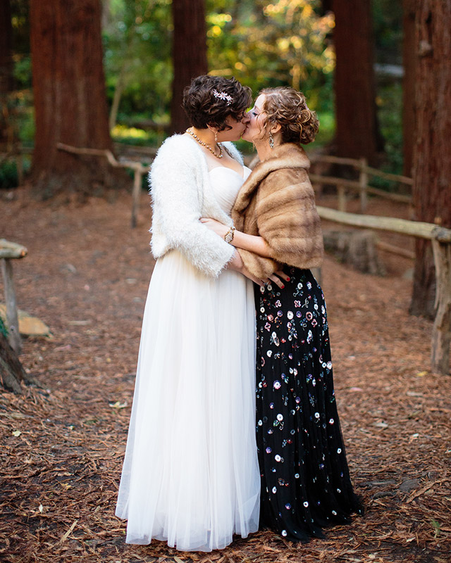 Two marriers, one in a white tulle gown and one in a black gown with beaded flowers, kiss beneath a grove of towering redwoods.