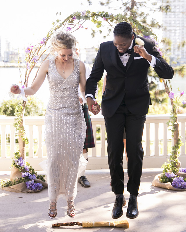 Two marriers, one in a beaded gown and one in a tux, hold hands before a grapevine arch and jump the broom at the end of their wedding ceremony.